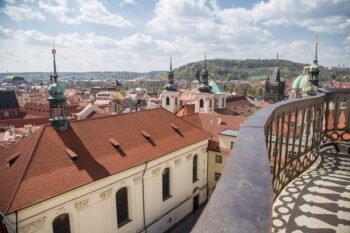 Geländer, Häuserdächer und Berge