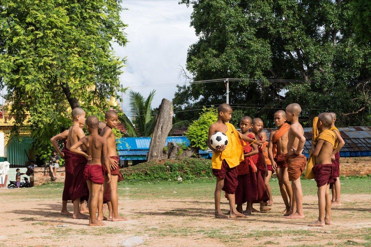 Die Nachwuchs-Mönche beim Fußballspielen vor der zerfallenen Pagode