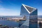 Wolkenkratzer mi herausragender Plattform und Stadt im Hintergrund