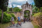 Jugendliche auf Fahrrädern bei einem Steintor