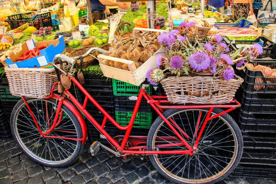 Fahrrad mit Körben mit Artischocken und Kastanien auf einem Markt