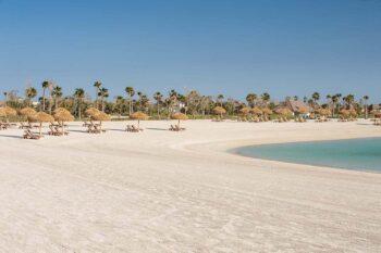 Strand mit Liegen und Sonnenschirmen in Doha