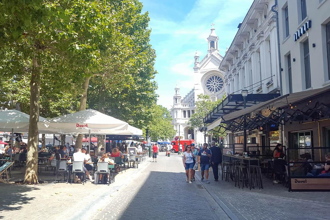 Straße mit Cafés und Kirche im Hintergrund