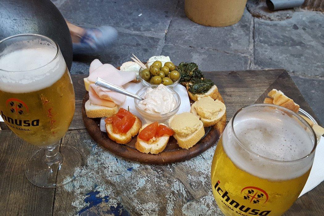 2 Bier und ein Teller mit belegten Broten und Oliven
