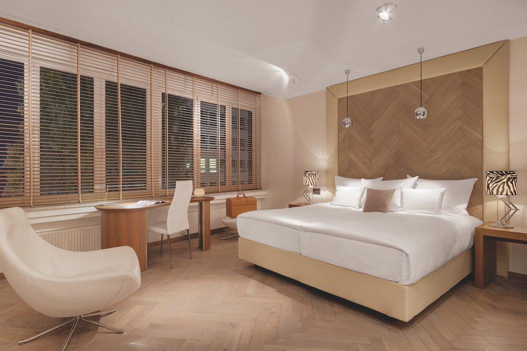 Großes Hotelzimmer mit warmen Farben und Doppelbett