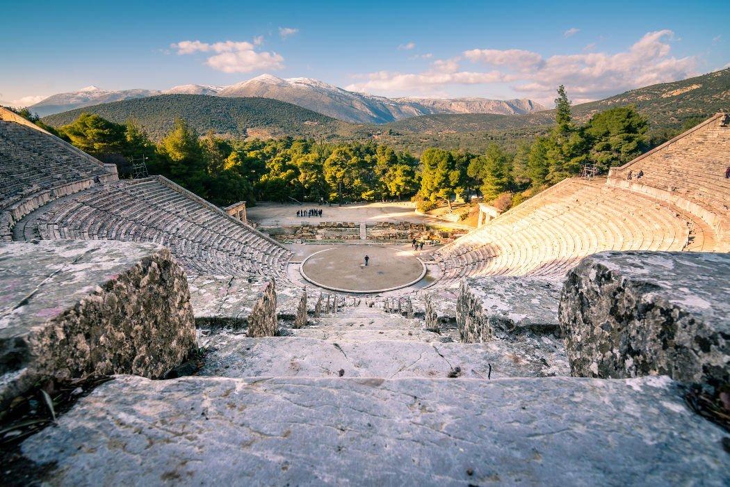 Blick in riesiges Theater aus Stein mit Bergen im Hintergrund