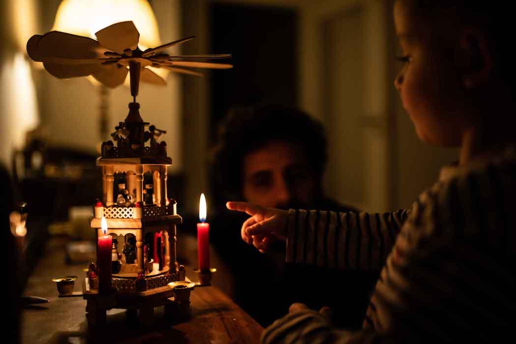 Kind neben Kerze und Weihnachtspyramide
