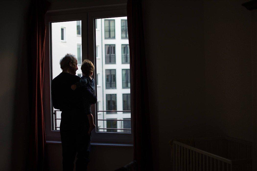 Großvater mit Kind im Arm schauen aus dem Fenster
