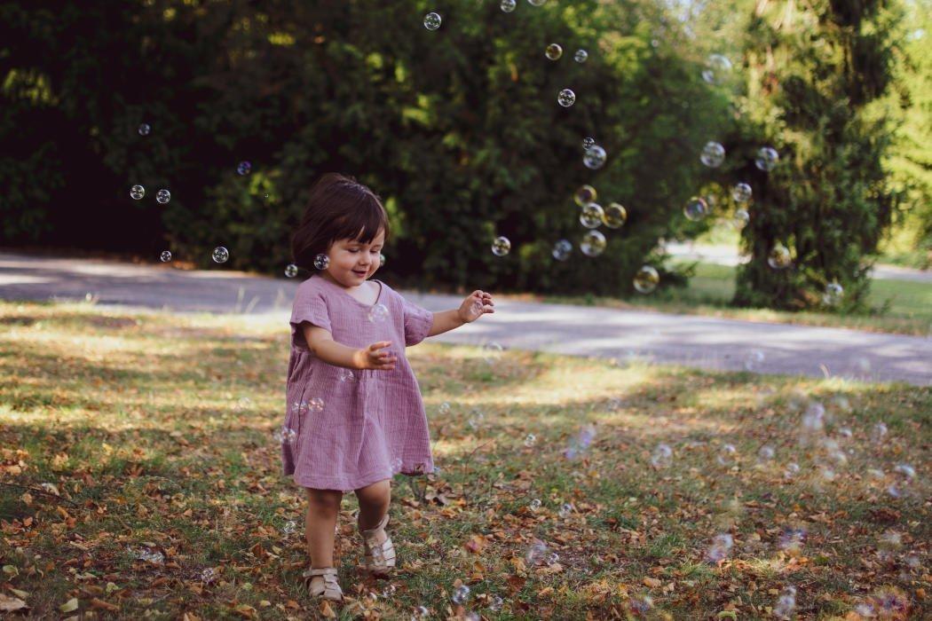 Mädchen spielt auf Wiese mit Seifenblasen
